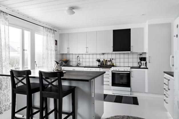 Snygg ljus färgskala och gott om förvaring i köket.