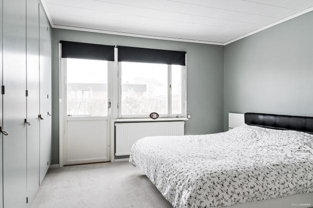 Sovrum med dörr ut till trädgården, textilmatta och garderobsvägg.