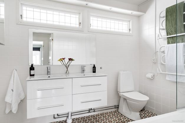 Helkaklat badrum med badkar, handdukstork, wc, dubbla handfat med kommod.