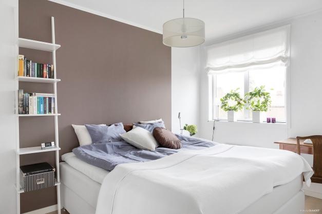 Sovrum med askparkettgolv och snygg fondvägg i mjuk färgskala.
