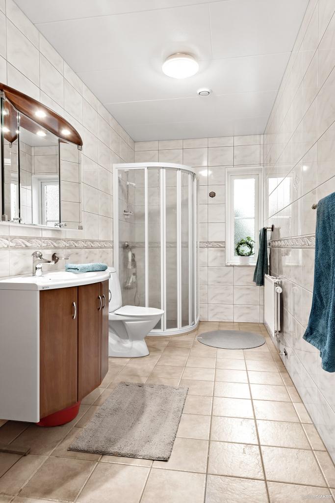 Badrum med dusch, wc och handfat. Kakel och klinker i neutrala färgval.
