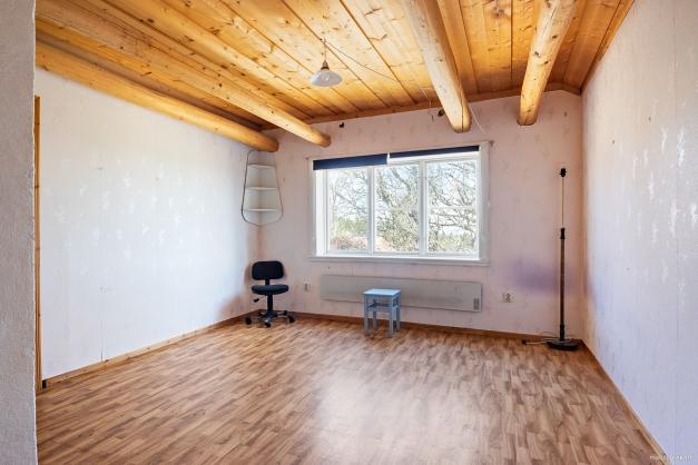 Stort sovrum på ovanplan med synliga balkar