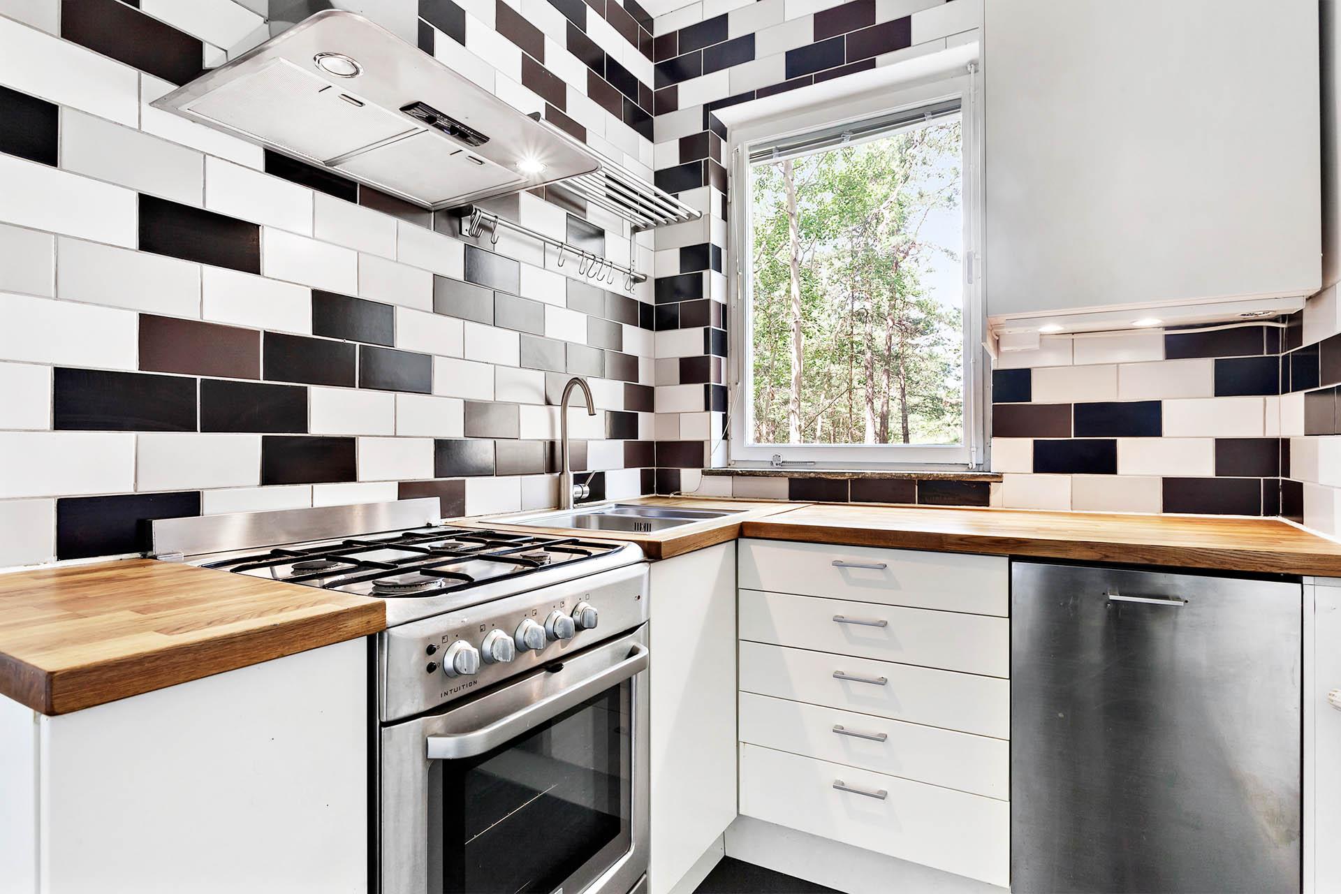 Kök med vit skåpsinredning och arbetsytor i massiv trä.