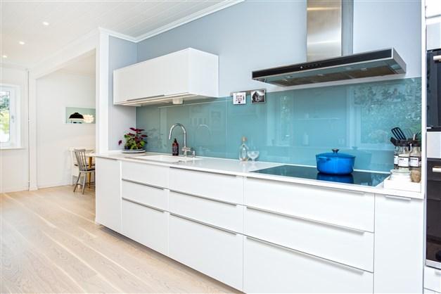 Över diskbänken sitter en glasskiva och arbetsbänkarna är av silsten.