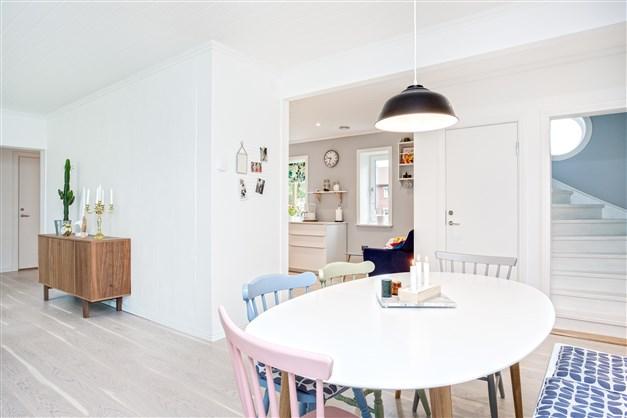 Öppen planlösning mellan kök och vardagsrum med plats för köksmöbel. Här finns också trappa till övervåningen och nedgång till källaren.