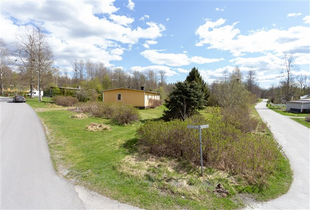 Huset ligger på en hörntomt med stor gräsyta.