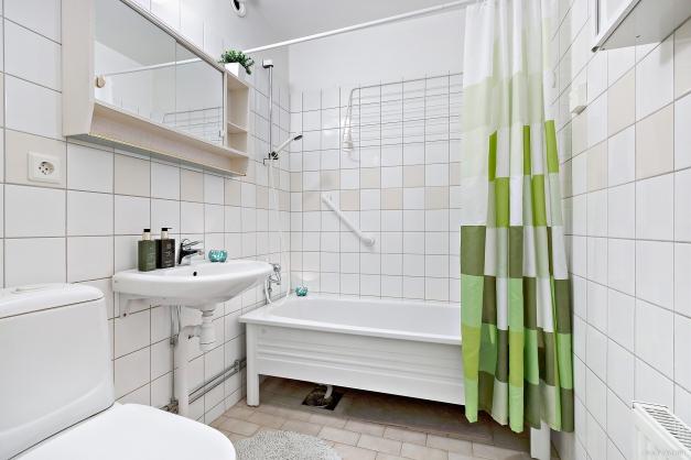 Helkaklat badrum med badkar.