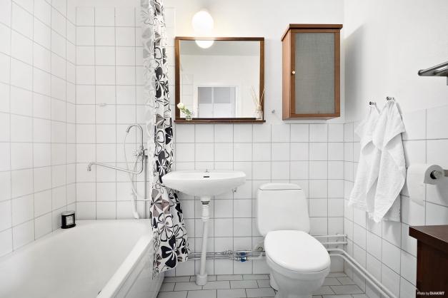 Ljust badrum med kakel och klinker.