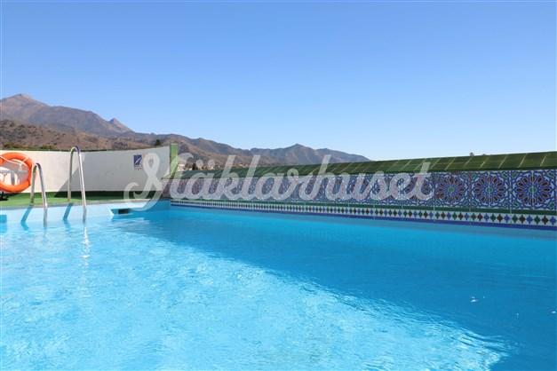 Gemensam pool på takterrassen med bergs- och havsutsikt