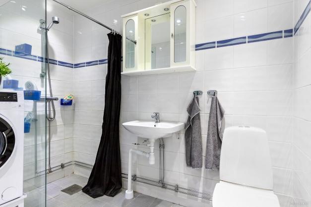 Helkaklat och frsächt badrum inrett med tvättmaskin.