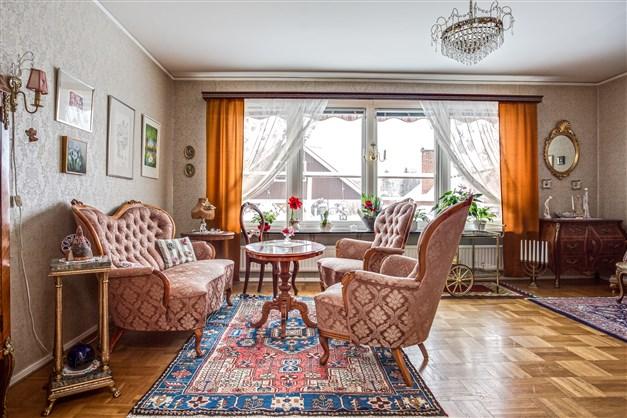 Vardagsrum med välskött orginalparkett och stora fönsterpartier som ger fint ljus.
