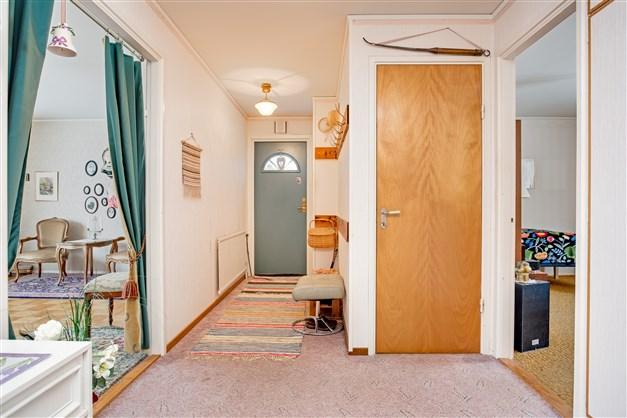 Hall med nedgång till källaren och uppgång till övervåningen. Här finns även städskåp och linneskåp med överskåp.