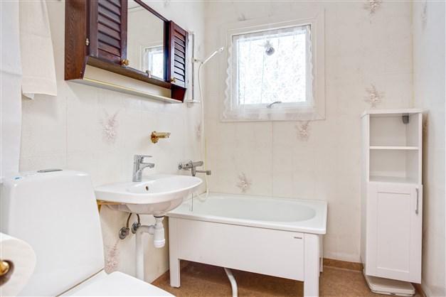 Badrum (äldre ytskikt) med nyare sittbadkar, wc och litet linneskåp.