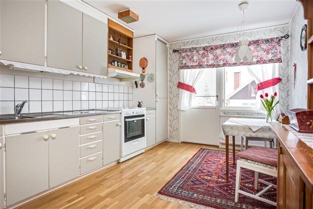 Ljust kök med renoverad orginalinredning, utgång till uteplats på baksidan och plats för mindre matmöbel i köket.