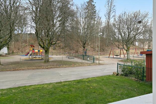 Vy från köksfönster mot lekplats och grönområden