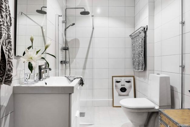 Ljust trevligt badrum med duschhörna och förberett för tvättmaskin.