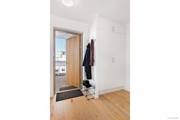 Entré sedd från vardagsrum med badrum till höger
