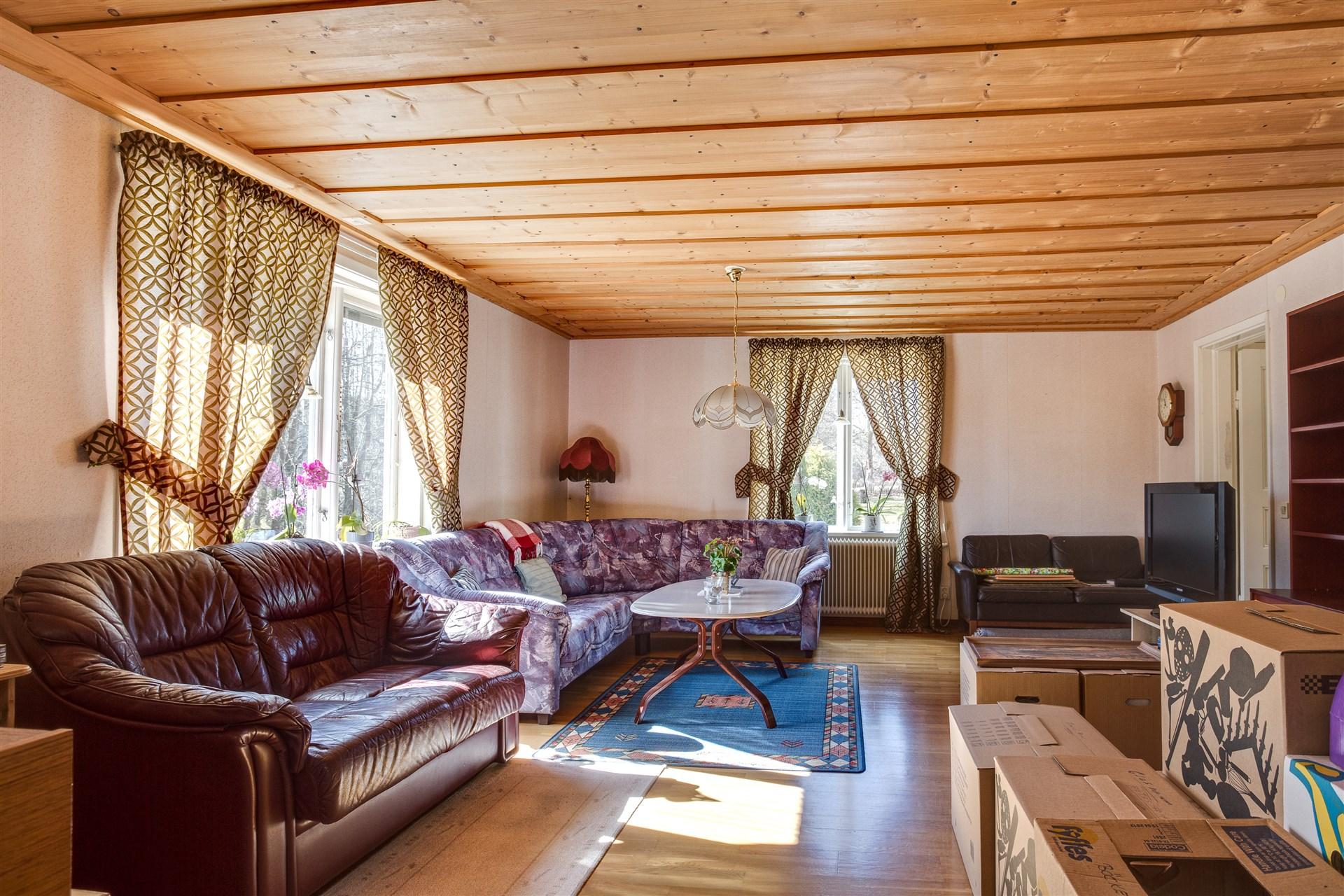 Vardagsrum med fint parkettgolv och breda plank i taket.