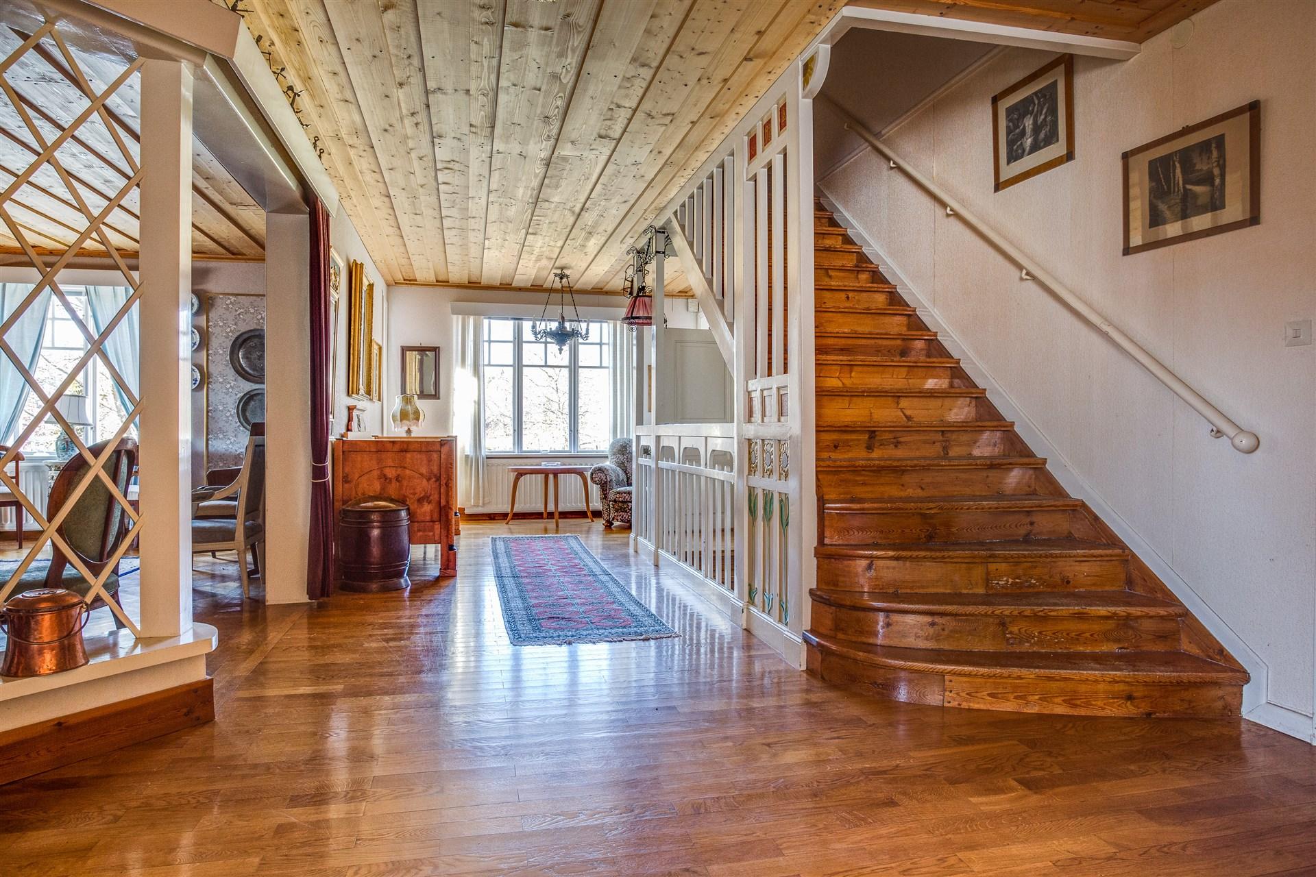 Hallen är möblerbar, har fin spaljé mot matsalen och har vacker trapp till vindsvåningen.