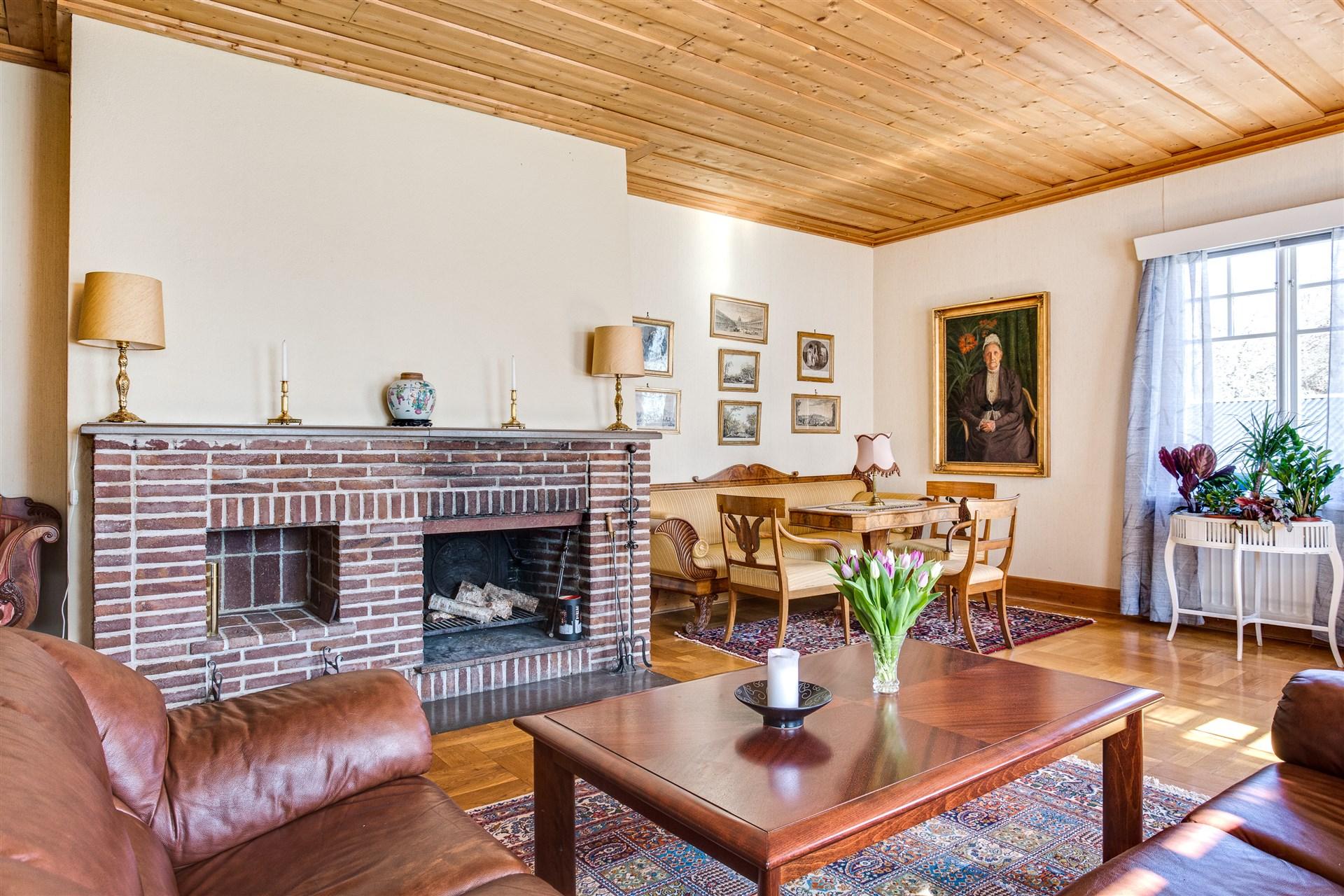 Vardagsrummet har en värmande eldstad och plats för flera möblemang.