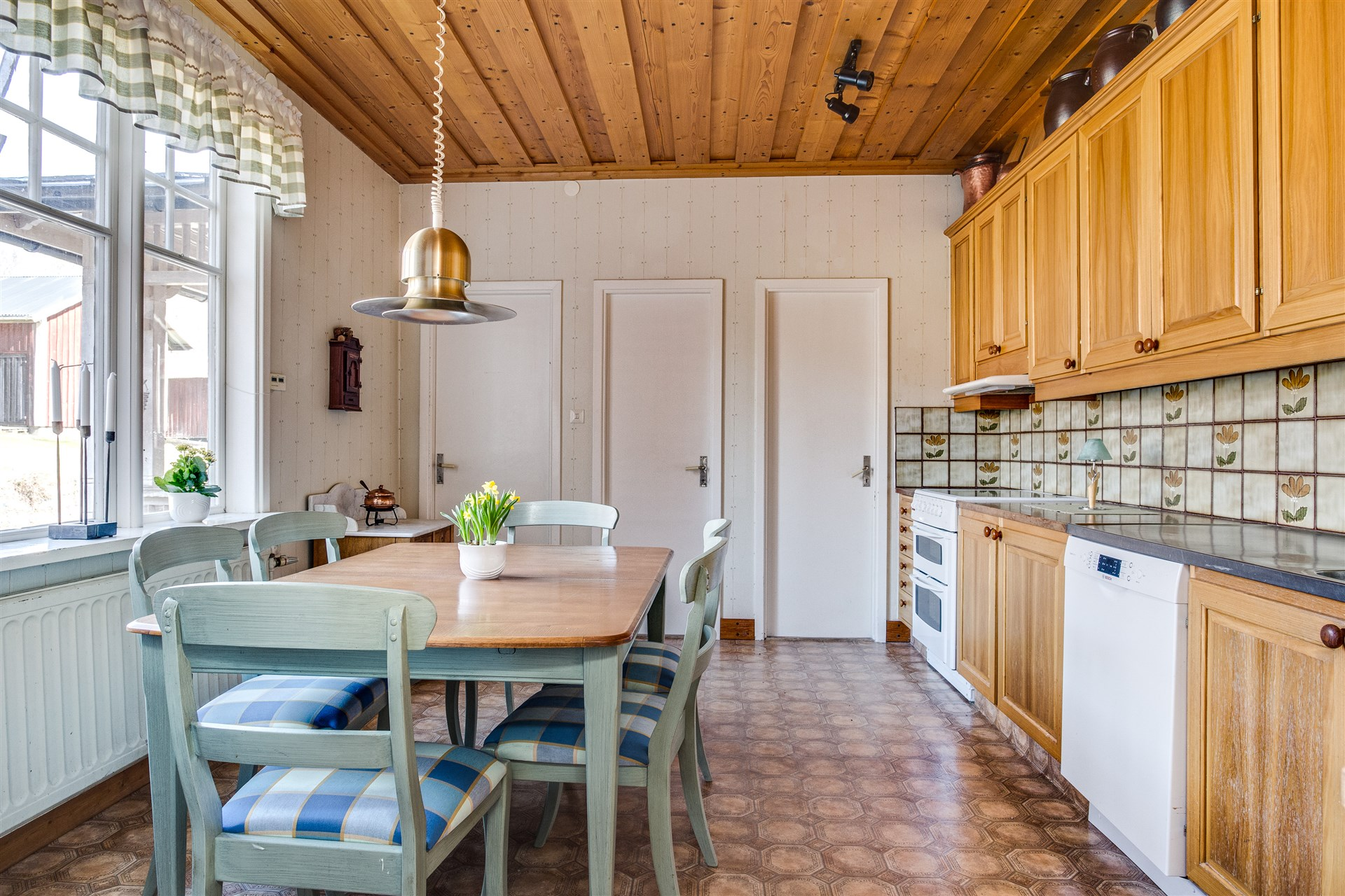 Kök med luckor i träslaget Alm. I köket finns uppgång till vindsdel 2 och utgång till baksidan, nedgång till källaren samt stort skafferi att gå in in med bra förvaring och arbetsbänk med över- och underskåp.