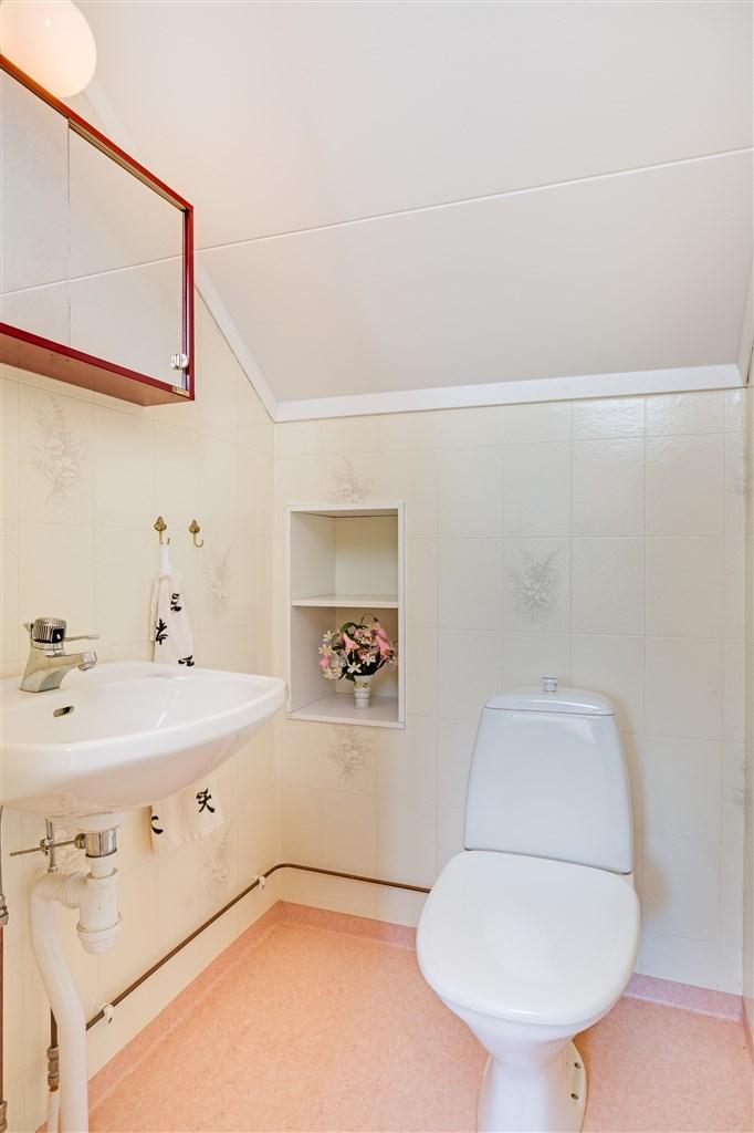 WC vid entré med liten inbyggd hylla i väggen.