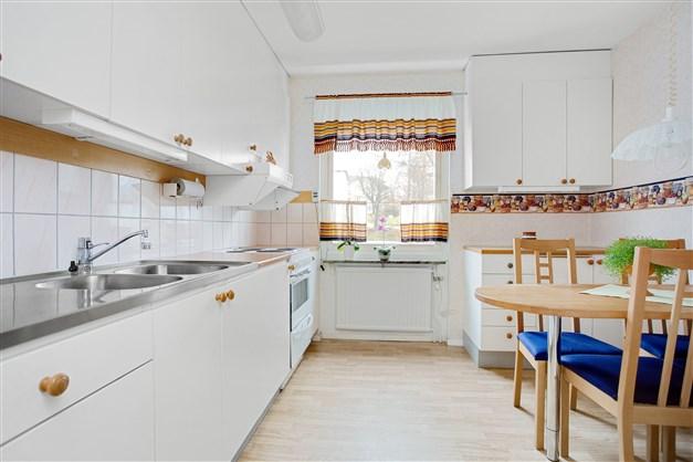 Ljust kök med vit inredning (Vedumkök) och fönster mot Centralvägen. Här finns bra arbetsyta och många skåp.