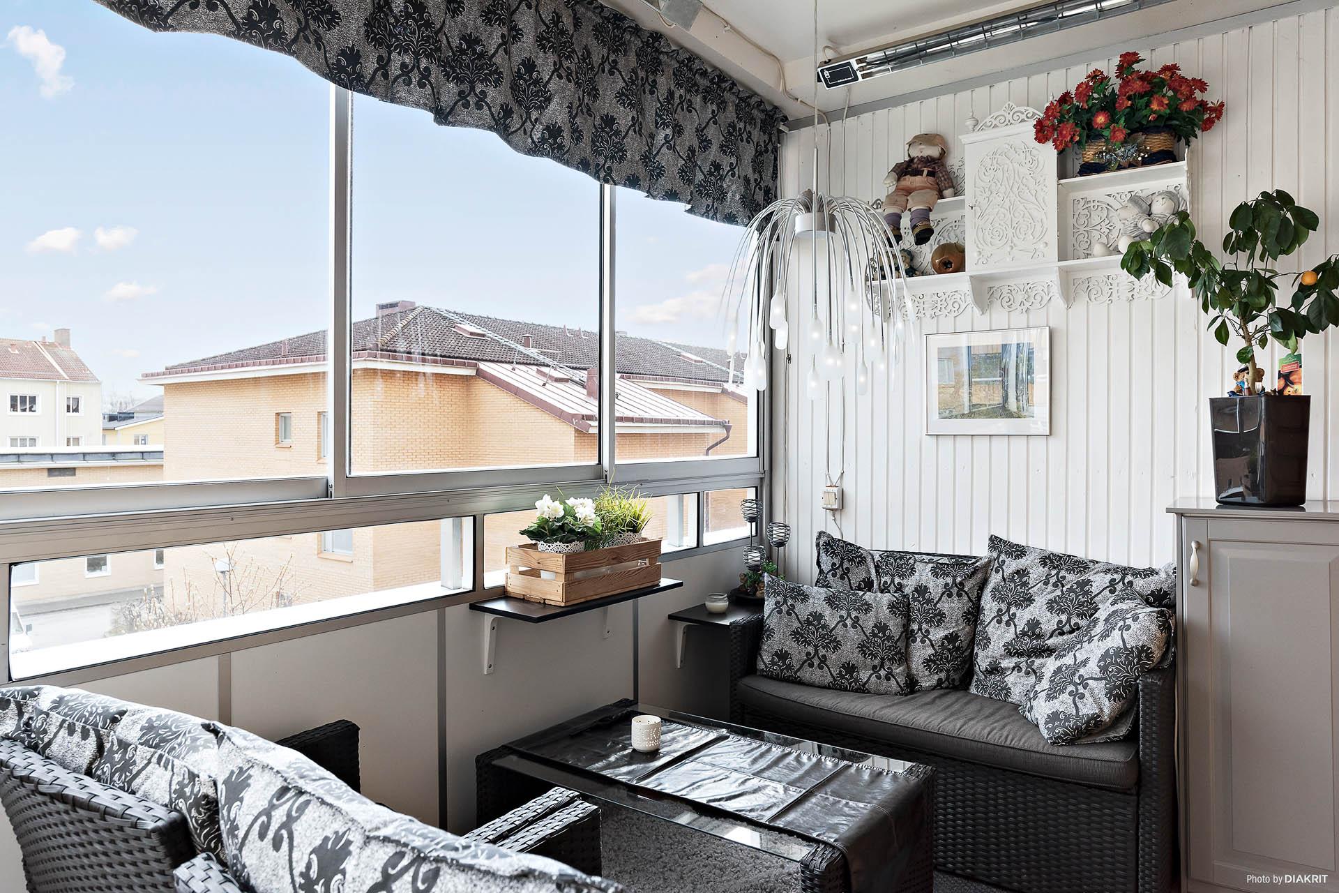 Inglasad balkong mot innergård med skjutbara fönsterpartier. Persienner för sol- och insynsskydd.