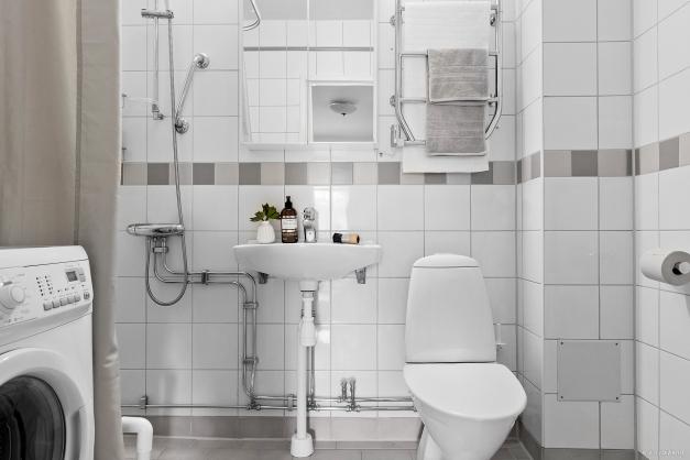 Helkaklat badrum med tvättmaskin och dusch
