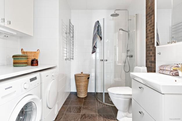 Helkaklat badrum med golvvärme och tvättdel.