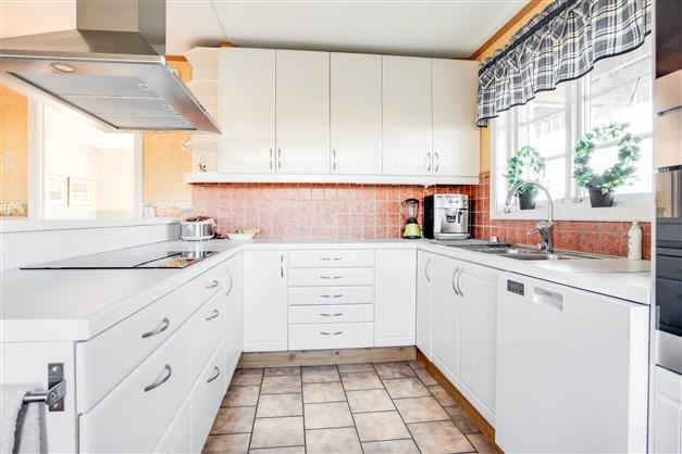 Köket har vit inredning och mycket arbetsyta.