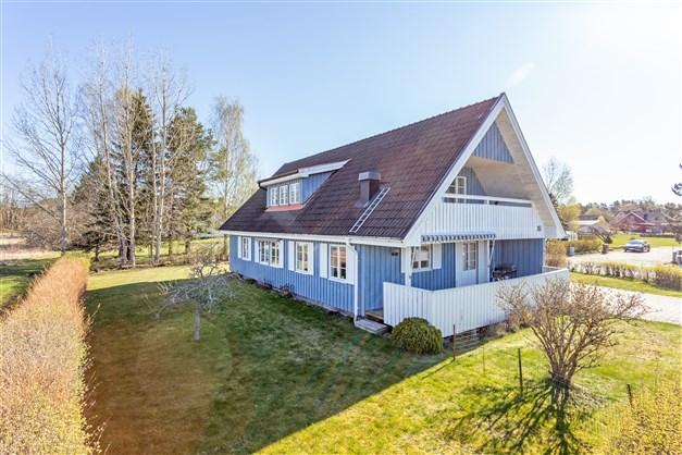 Huset är inramat med en häck runtom, samt mindre träddunge.
