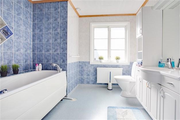 Ljust badrum med stort fönster som ger mycket ljus.