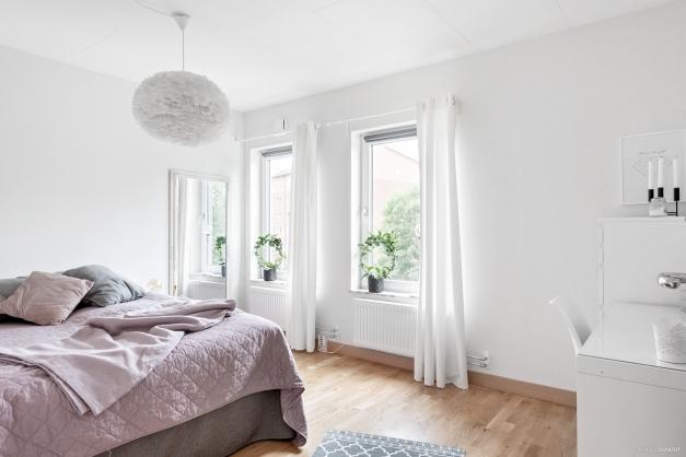 Sovrum 1 av 2 med plats för en större säng och kompletterande nattduksbord