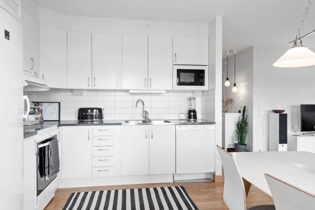 Stilrent kök med vita skåpsluckor, vitt kakel och mörkare bänkskiva