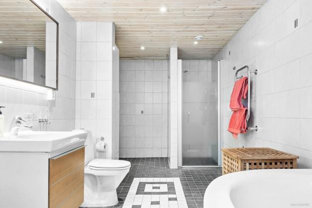 Stort helkaklat badrum/tvättrum med både dusch, badkar, tvättmaskin och torktumlare