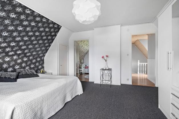 Storslaget sovrum 4 på övre plan med ombonad grå textilmatta på golv. Under textilmattan finns parkett om man önskar ta fram den.