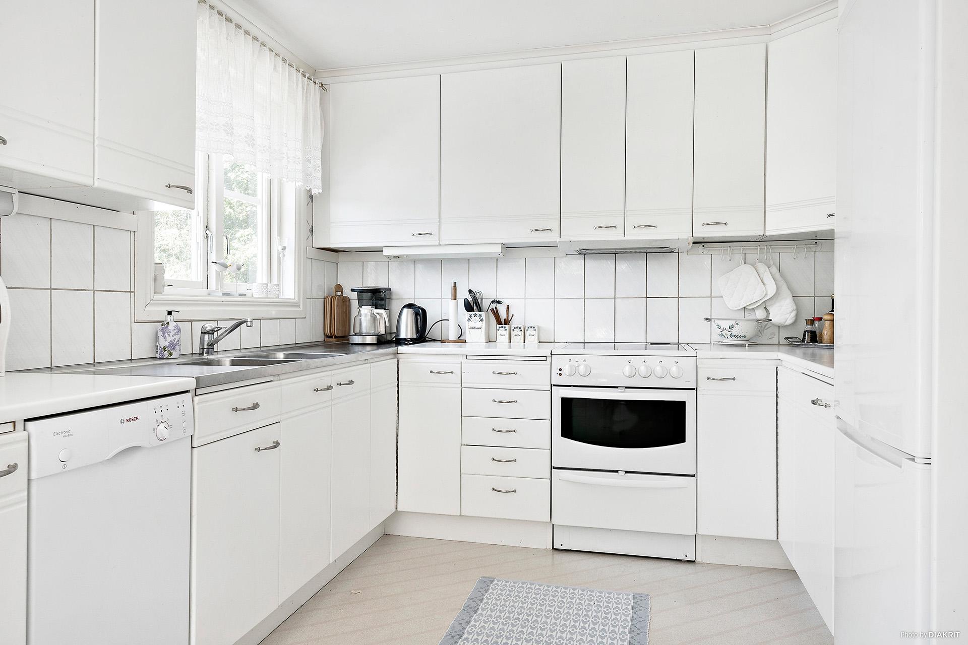 Vitt kök med goda förvaringsmöjligheter och arbetsytor