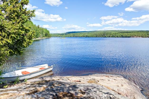 Gussjön ligger nedanför stugan med båt och badklippor
