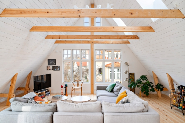 Det stora vardagsrummet har fönster både högt och lågt samt full takhöjd hela vägen upp till nock