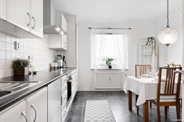 Praktiskt och ljust kök i svart och vitt med rostfria vitvaror.