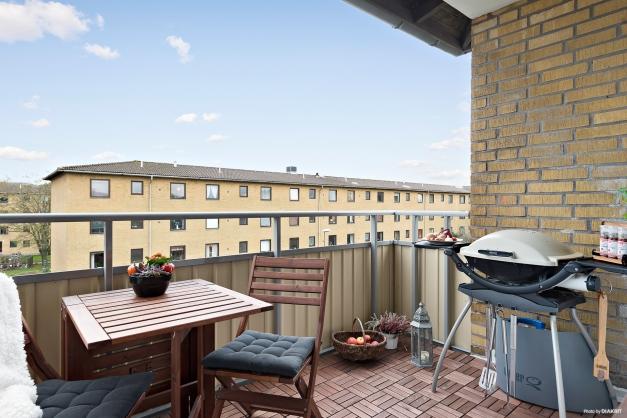 Insynsskyddad balkong med trall och plats för bord och grill.