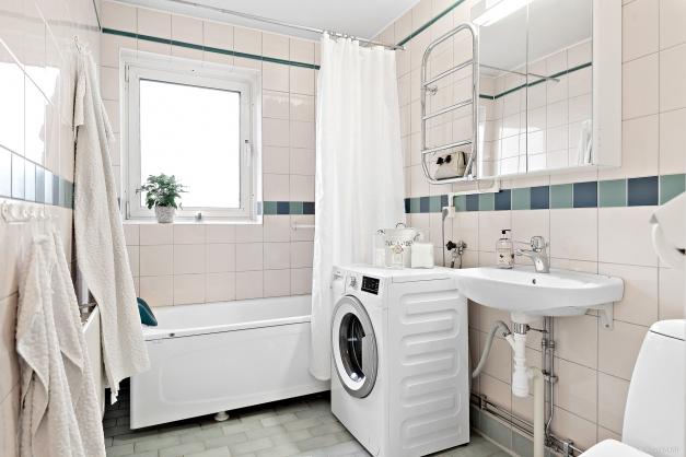 Helkaklat badrum med fönster. Badkar, WC, handfat och tvättmaskin. Spegelskåp med förvaring samt handdukstork.