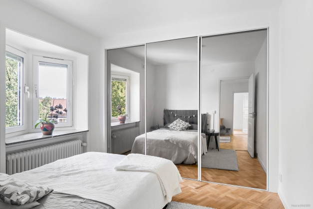 Sovrum med bra förvaring i skjutdörrsgarderob med spegeldörrar
