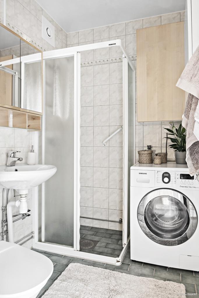 Helkaklat badrum inrett med kombinerad tvättmaskin/torktumlare.