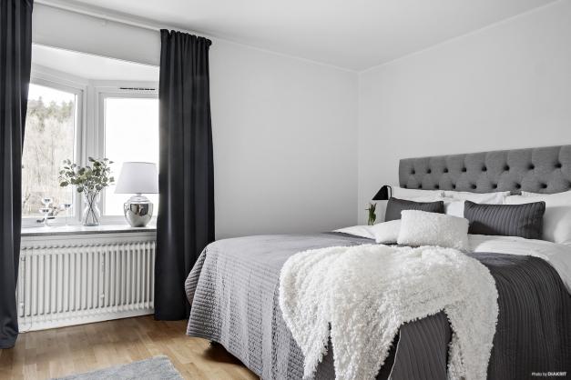 Mysigt sovrum med plats för stor säng och nattduksbord.