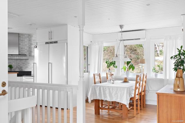 Rymlig matplats i köket med utgång till terrassen samt trappan som leder er till bastun på berget.