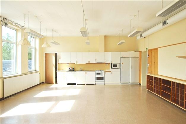 Vardagsrum med öppen planlösning mot kök i tänkt lägenhet