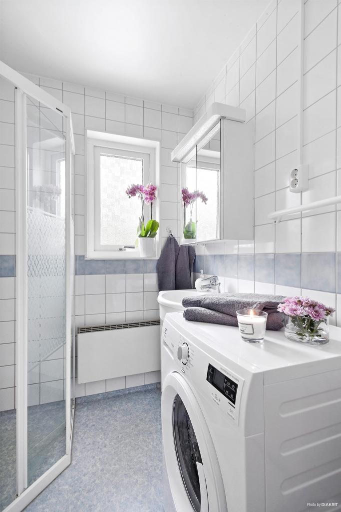 Badrum med fönster och tvättmaskin