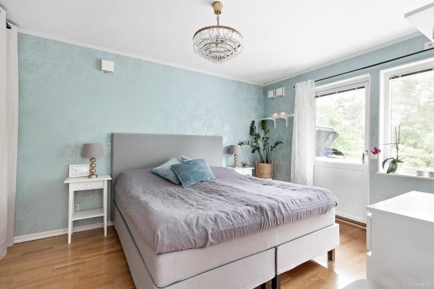 Sovrum med hel garderobsskåpsvägg och utgång till balkong
